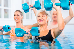 People young and senior in water gymnastics physiotherapy with dumbbells