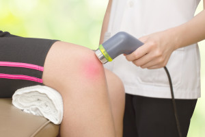 Physical therapist using ultrasound probe on woman patient 's knee for release pain