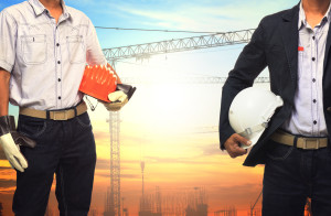 Two Engineer Man Working With White Safety Helmet Against Crane